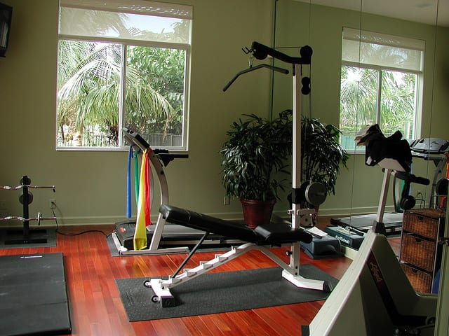 An open custom gym with free weights and exercise machines.